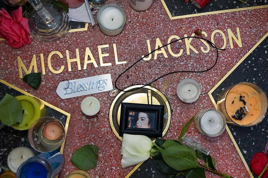 This June 27, 2009 file photo shows the star of US music legend Michael Jackson on the Hollywood Walk of Fame on Hollywood Boulevard in Los Angeles,CA adorned with offerings from fans after he died on June 25, 2009. -- PHOTO: AFP