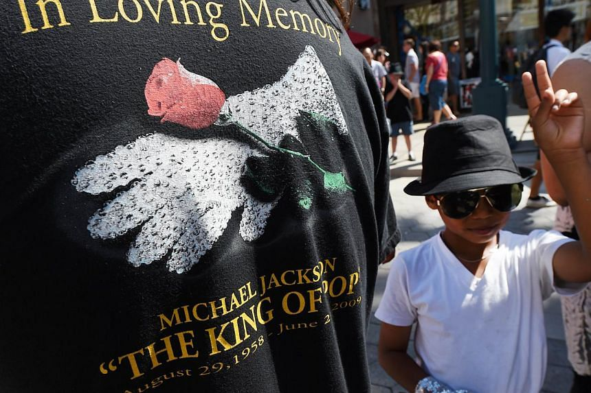 A young Michael Jackson impersonator gestures after performing in a Michael Jackson tribute flash mob dance on the 3rd Street Promenade in Santa Monica, California on June 22, 2014. -- PHOTO: AFP