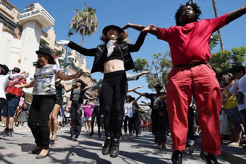 People perform a Michael Jackson Tribute flash mob dance on the 3rd Street Promenade in Santa Monica, California on June 22, 2014. -- PHOTO: AFP