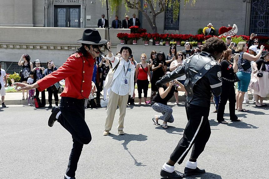 Michael Jackson impersonators Rem Garza (left) and Lorenzo Coleman (right) perform in front of fans gathered for the 5th anniversary of Jackson's death at Forest Lawn Memorial Park-Glendale in Glendale, California June 25, 2014. -- PHOTO: REUTERS