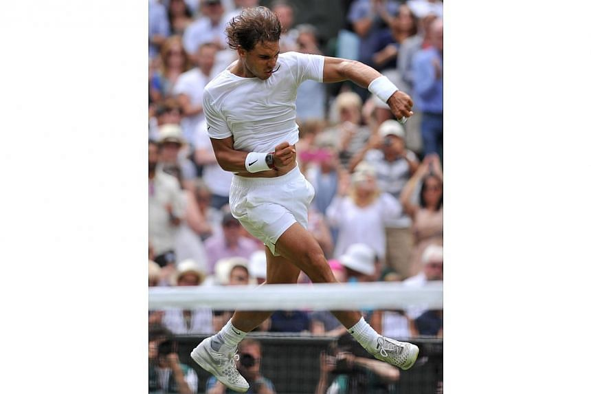 Spain's Rafael Nadal jumps and punches the air as he celebrates beating Czech Republic's Lukas Rosol during their men's singles second round match on day four of the 2014 Wimbledon Championships at The All England Tennis Club in Wimbledon, southwest