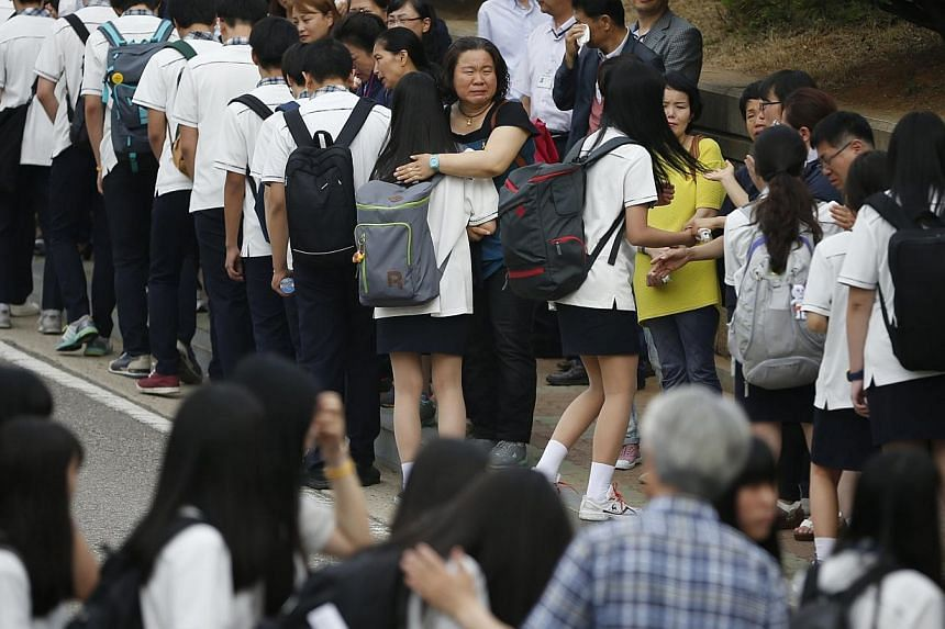 Relatives of the April 16 ferry disaster victims comfort students who survived the accident as they make their way back to school in Ansan June 25, 2014. The daughter of a crew member of a South Korean ferry which sank killing hundreds of school