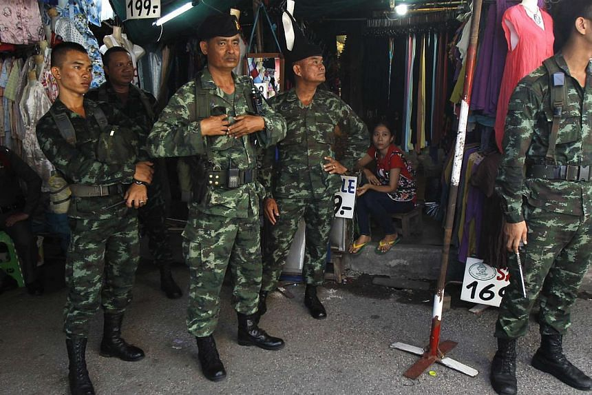 Soldiers stand guard at a shop at Chatuchak market in Bangkok on June 8, 2014. A senior Thai general has rejected reports that the army planned to rid the kingdom of the influence of controversial former premier Thaksin Shinawatra years before it sei