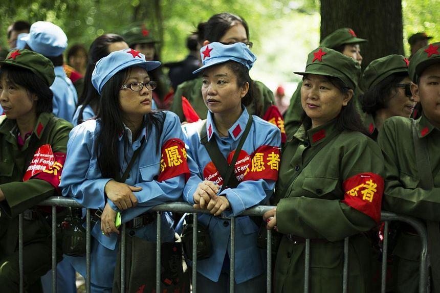 People wear communist-era uniform costumes as they wait to meet Chinese billionaire Chen Guangbiao during a lunch he sponsored for hundreds of needy New Yorkers at The BoatHouse in New York's Central Park on June 25, 2014. -- PHOTO: REUTERS