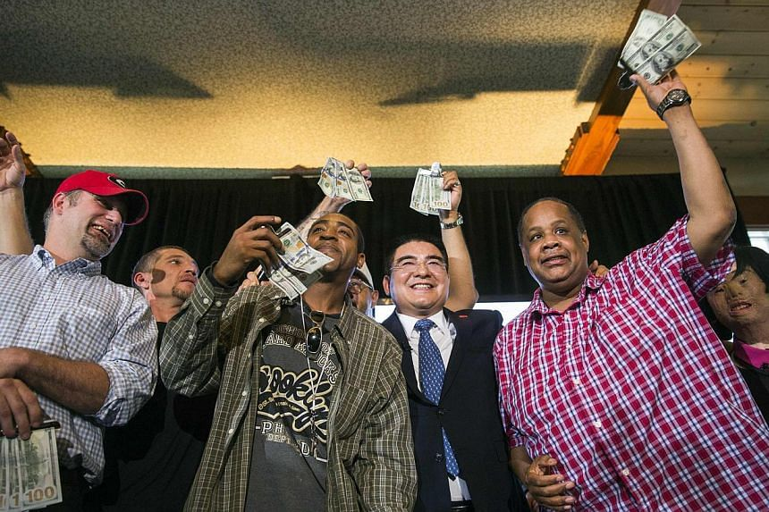 Chinese billionaire Chen Guangbiao stands with men to whom he has given US$300 during a lunch he sponsored for hundreds of needy New Yorkers at TheBoatHousein New York's Central Park on June 25, 2014. -- PHOTO: REUTERS