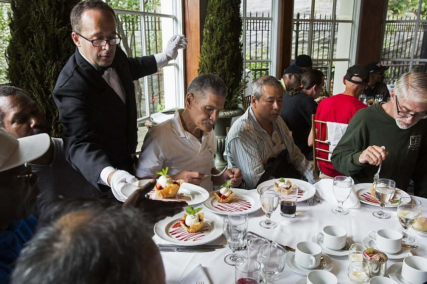 A waiter serves dessert to a table of men listening to Chinese billionaire Chen Guangbiao during a lunch he sponsored for hundreds of needy New Yorkers at TheBoatHousein New York's Central Park on June 25, 2014. -- PHOTO: REUTERS