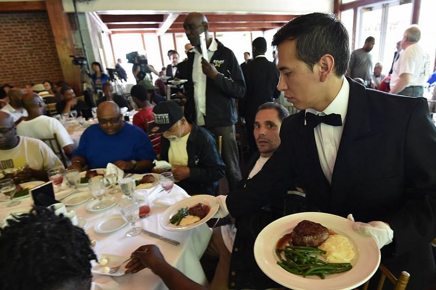 A waiter serves meals as Chinese philanthropist Chen Guangbiao hosts a lunch for several hundred homeless people from the New York City Rescue Mission on June 25, 2014 at The Boathouse restaurant in New York's Central Park. -- PHOTO: AFP