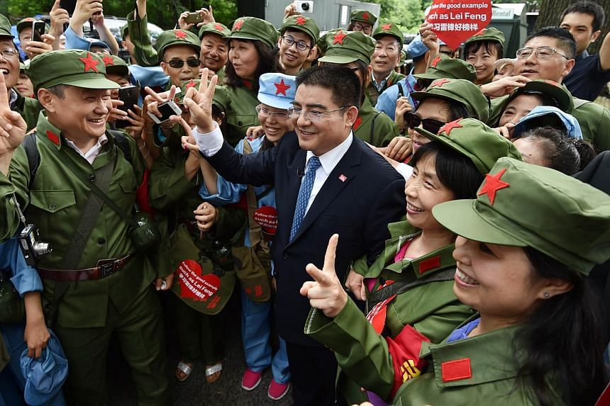 Chinese philanthropist Chen Guangbiao (centre) greets volunteers dressed in green Chinese military uniforms (left) before hosting a luncheon for several hundred homeless people on June 25, 2014 at The Boathouse restaurant in New York's Central Park.