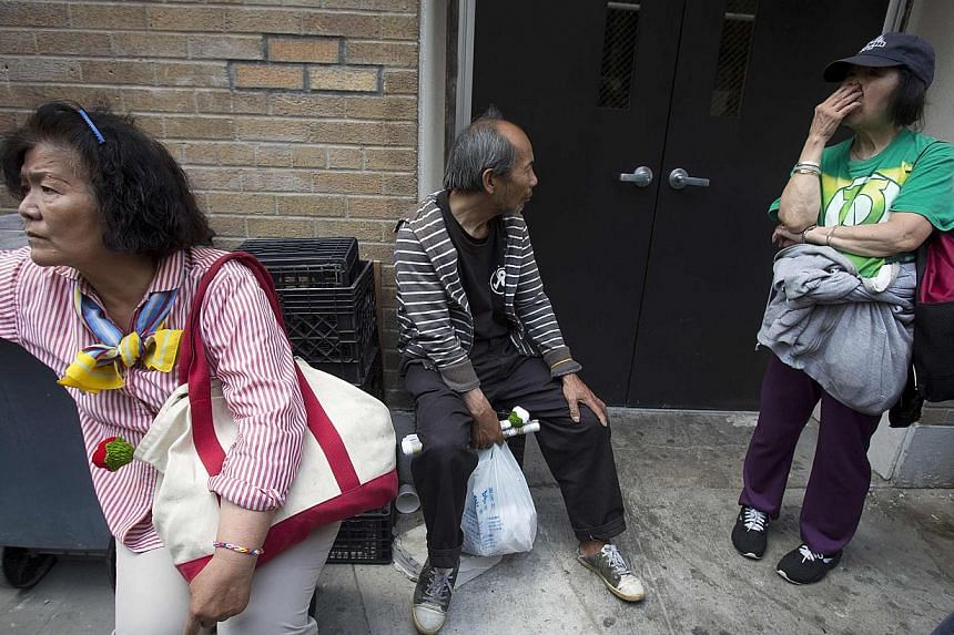 People react after finding out they will not be receiving money that they had been promised outside the New York Rescue Mission in the Manhattan borough of New York on June 25, 2014. -- PHOTO: REUTERS