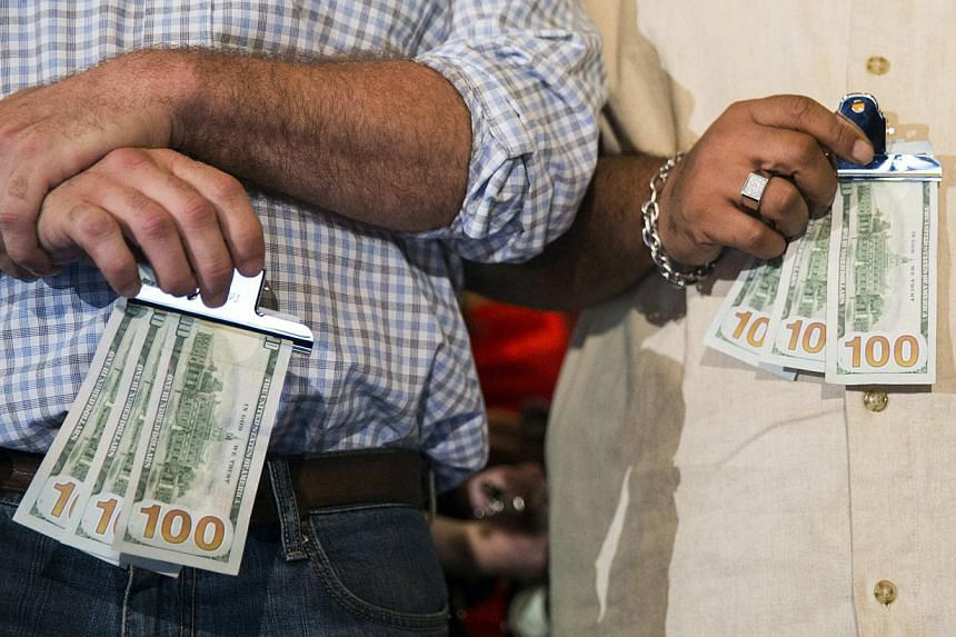 Men hold US$300 in cash given to them by Chinese millionaire Chen Guangbiao during a lunch he sponsored for hundreds of needy New Yorkers at TheBoathouse in New York's Central Park on June 25, 2014. -- PHOTO: REUTERS