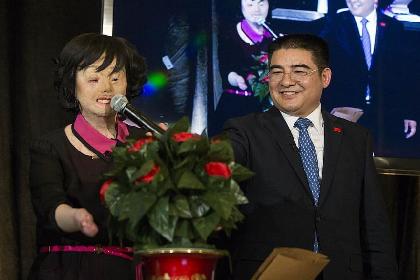 Chinese millionaire Chen Guangbiao applauds as self-immolation victim Chen Guo leads a singalong of a Chinese song during a lunch he sponsored for hundreds of needy New Yorkers at The Boathouse in New York's Central Park on June 25, 2014. -- PHOTO: R