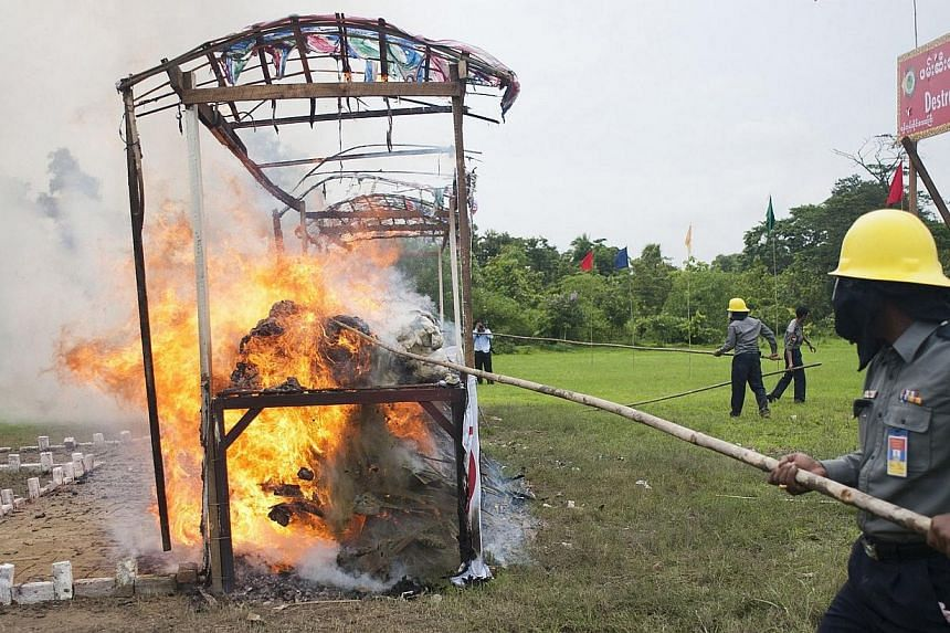 "Piles of seized drugs burn after being set on fire during a ceremony to mark the UN's ""International Day against Drug Abuse and Illicit Trafficking"" in Yangon on June 26, 2014. -- PHOTO: AFP"