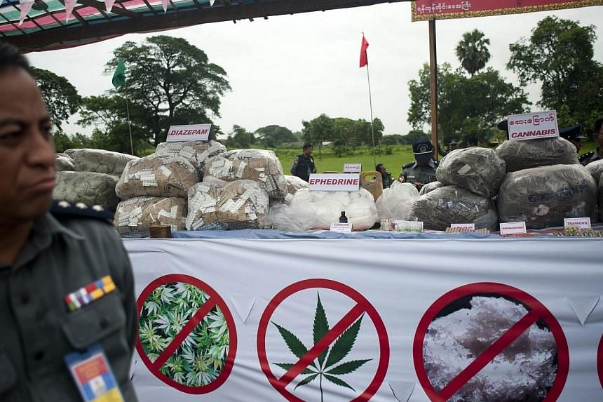 "Myanmar police stand beside seized drugs before they are destroyed during a ceremony to mark the UN's ""International Day against Drug Abuse and Illicit Trafficking"" in Yangon on June 26, 2014. -- PHOTO: AFP"
