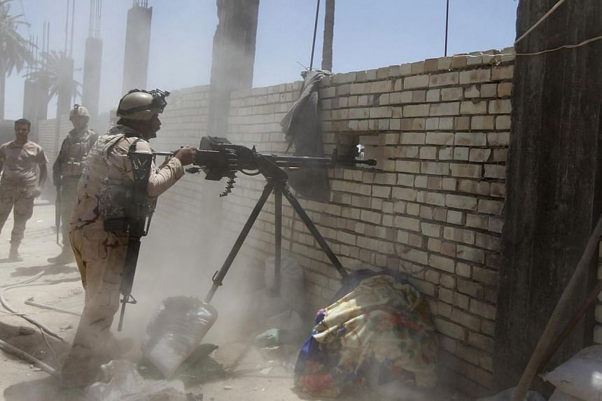 A member of the Iraqi security forces opens fire during clashes with fighters from Sunni militant group Islamic State of Iraq and the Levant (ISIL) in Ibrahim bin Ali village, west of Baghdad on June 24, 2014. IraqPrime Minister Nouri al-Maliki