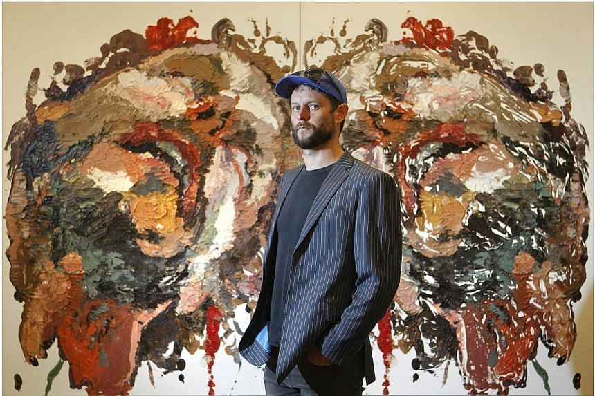 "Australian artist Ben Quilty with his painting ""Smashed Rorschach"" at the exhibition preview of the inaugural Prudential Eye Awards for Contemporary Asian Art in Suntec City Mall on Jan 17, 2014. An exhibition on contemporary Singapore art will"
