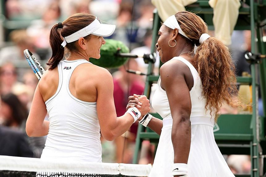 US player Serena Williams (right) shakes hands with Russia's Chanelle Scheepers after winning their women's singles second round match on day four of the 2014 Wimbledon Championships at The All England Tennis Club in Wimbledon, south-west London, on
