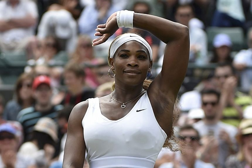 Serena Williams of the United States waves after defeating Chanelle Scheepers of South Africa in their women's singles tennis match at the Wimbledon Tennis Championships in London on June 26, 2014. -- PHOTO: REUTERS