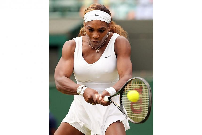 US player Serena Williams returns to Russia's Chanelle Scheepers during their women's singles second round match on day four of the 2014 Wimbledon Championships at The All England Tennis Club in Wimbledon, south-west London, on June 26, 2014. --