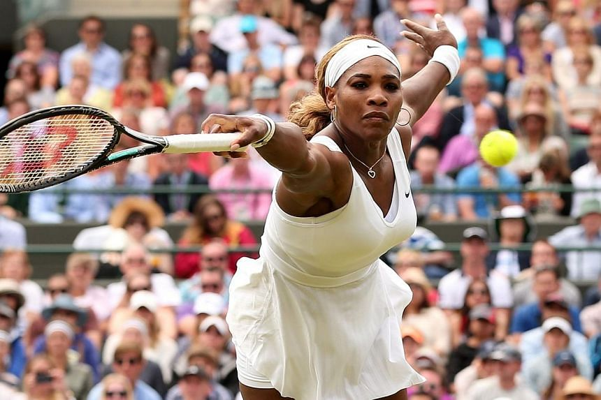 US player Serena Williams returns to Russia's Chanelle Scheepers during their women's singles second round match on day four of the 2014 Wimbledon Championships at The All England Tennis Club in Wimbledon, south-west London, on June 26, 2014. -- PHOT
