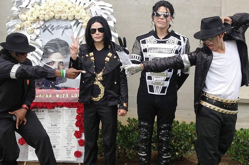 Four Michael Jackson impersonators pose outside of Jackson's mausoleum at the Forest Lawn Memorial Park cemetery in Glendale, California on the 5th anniversary of Jackson's death on June 25, 2014. -- PHOTO: AFP