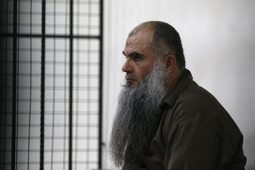Radical Muslim cleric Abu Qatada looking on from behind bars at the State Security Court in Amman on June 26, 2014.The court acquitted him on Thursday regarding charges of conspiring to commit acts of terrorism. The cleric, who was extradited f