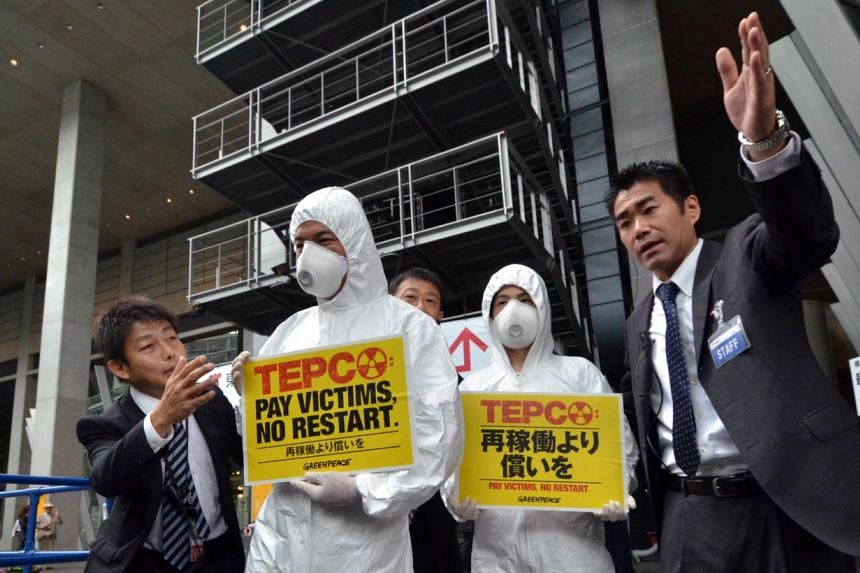 Members of environmental group Greenpeace wearing radiation protection suits are asked by Tepco staff to move away from the entrance of a company shareholders' meeting in Tokyo on Thursday. Activists wore full protective suits and industrial fac