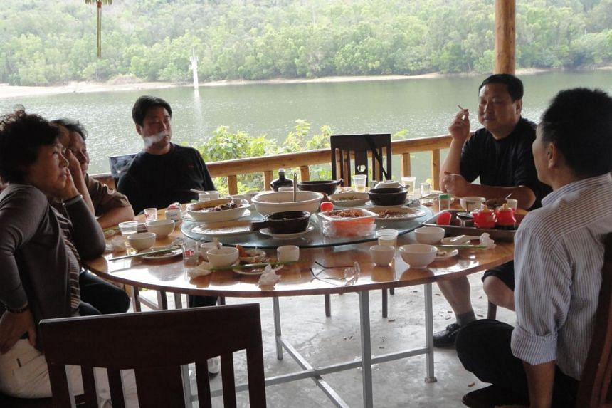 Activist Xu Xiangyu (left) and her husband (2nd left, partly obscured) at lunch in March 2011 with court and police officials who escorted her on a forced vacation to China's southern Hainan Island. Xu is one of dozens of campaigners who rights group