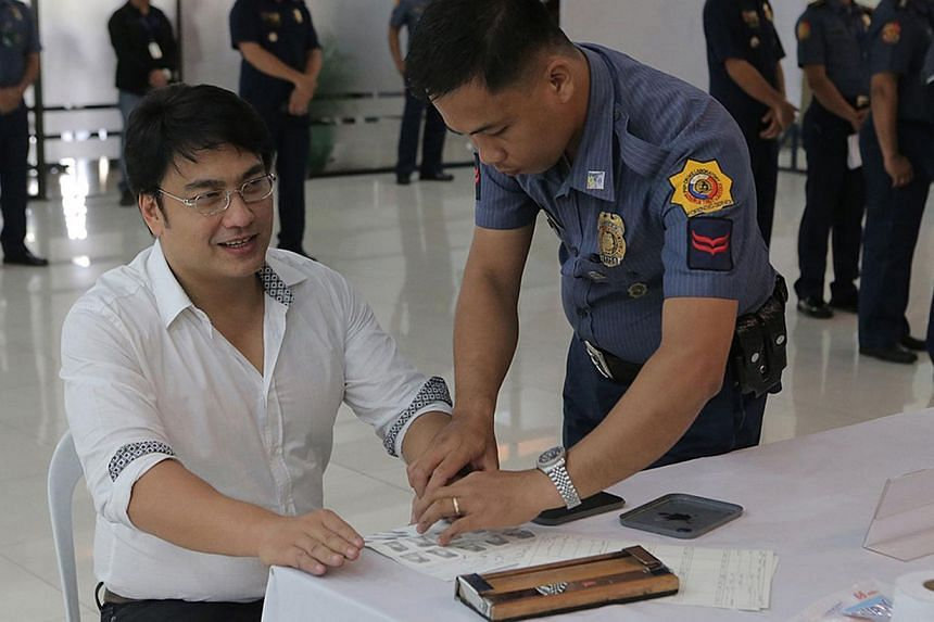 This handout photo released by the Philippine National Police (PNP) shows Philippine Senator Ramon Bong Revilla (centre) having his fingerprints taken at the PNP headquarters before he is brought to his detention cell on June 20, 2014. -- PHOTO: AFP