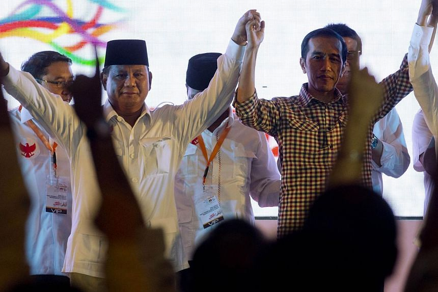 Indonesian presidential candidates Prabowo Subianto (left) and Joko Widodo joining hands on stage after signing a declaration calling for peaceful elections during a ceremony on June 3 in Jakarta.