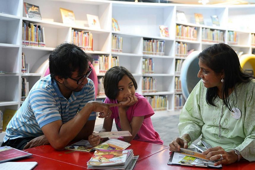 These bookmarks are among the materials designed by ST artist Lee Chee Chew that use humour to influence social behaviour. Volunteer Saberah Begum (right), a pre-school teacher, passing a bookmark and explaining good library habits to Zuhairah Ubaidi