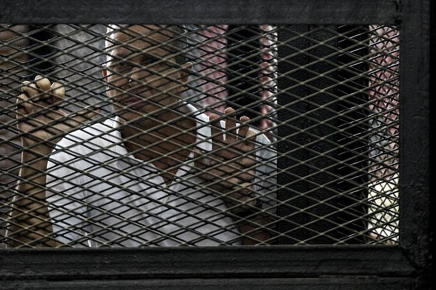 Al-Jazeera news channel's Australian journalist Peter Greste listens to the verdict inside the defendants cage during his trial for allegedly supporting the Muslim Brotherhood on June 23, 2014. -- PHOTO: AFP