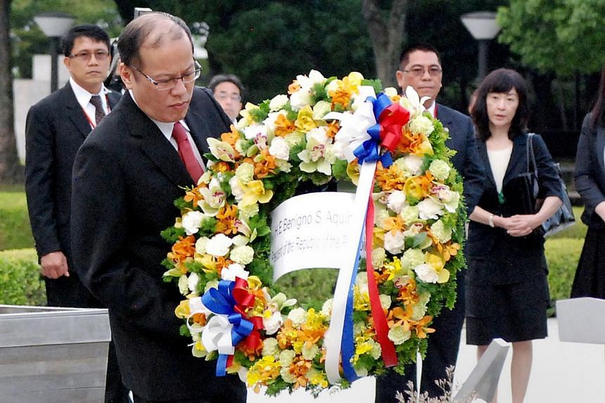 Philippine President Benigno Aquino (front left) lays a weath on an altar for the A-bomb victims at the Peace Memorial Park in Hiroshima on June 24, 2014. -- PHOTO: AFP