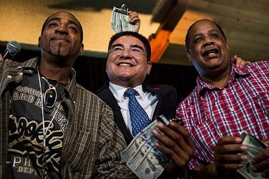 Mr Chen Guangbiao (centre), a Chinese recycling magnate worth approximately $400 million and the self-proclaimed most influential person of China, poses for a photo with two homeless men, who he gave $300 to during a lunch he hosted for approximately