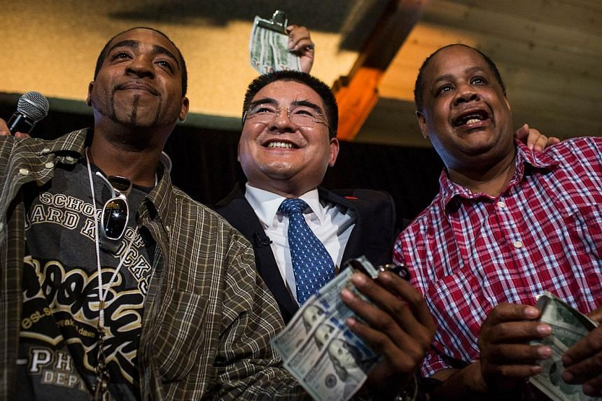 Chen Guangbiao (centre), a Chinese recycling magnate worth approximately $400 million and the self-proclaimed most influential person of China, poses for a photo with two homeless men, who he gave $300 to during a lunch he hosted for approximately 20