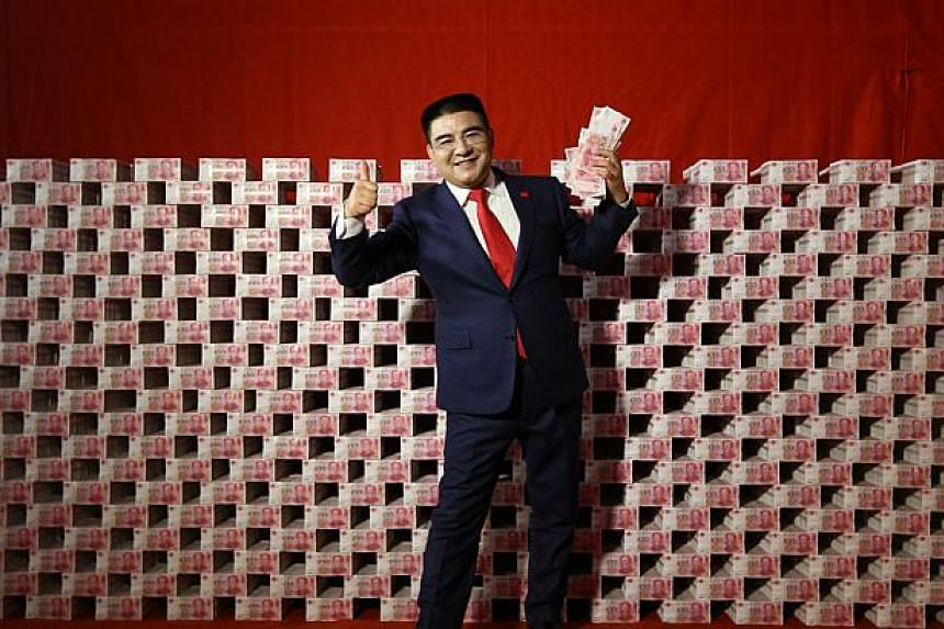 Chen posing in front of a wall of cash, a stunt the Chinese millionaire is famous for. -- PHOTO: HUFFINGTON POST