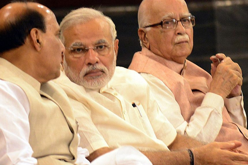 Indian Prime Minister Narendra Modi (C) talks with Bharatiya Janata Party (BJP) President and Indian Minister of Home Affairs Rajnath Singh (L) as senior BJP leader Lal Krishna Advani looks on during the BJP parliamentary party meeting in New Delhi o
