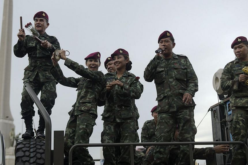 Thai soldiers sing as they stand on an army truck to entertain people at Victory monument in Bangkokon June 5, 2014. -- PHOTO: AFP