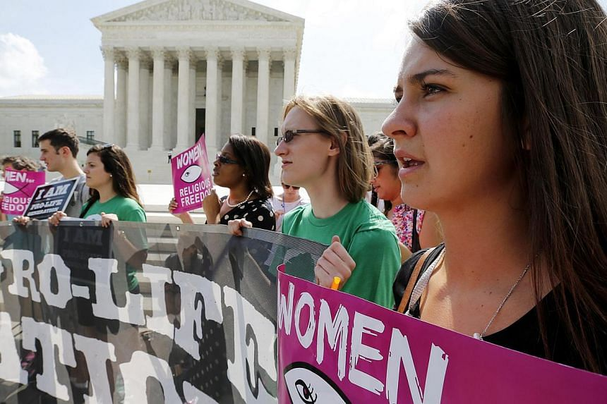 Anti-abortion protestors sing as they await the U.S. Supreme Court's ruling on a Massachusetts law that mandated a protective buffer zone around abortion clinics, outside the Court in Washington on June 26, 2014. -- PHOTO: REUTERS