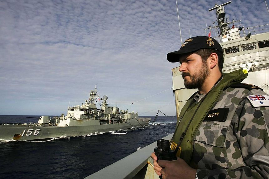 A file handout photo taken on April 7, 2014 and released on April 11 by the Australian Defence shows Able Seaman Maritime Logistics – Steward Kirk Scott keeping watch on the forecastle of auxiliary oiler HMAS Success as they conduct a Replenishment