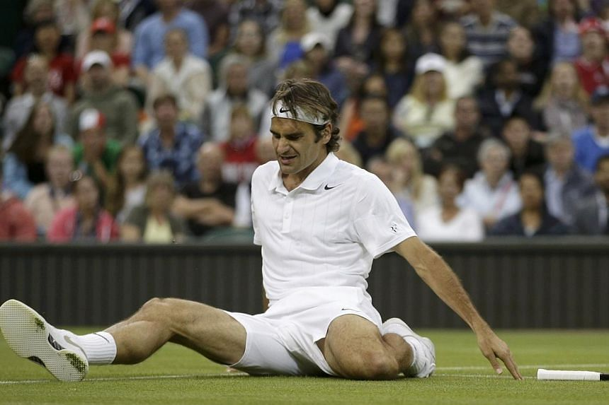 Roger Federer of Switzerland slips during their men's singles tennis match against Gilles Muller of Luxembourg on Centre Court at the Wimbledon Tennis Championships in London on June 26, 2014. Wimbledon's head groundsman Neil Stubley is relaxed