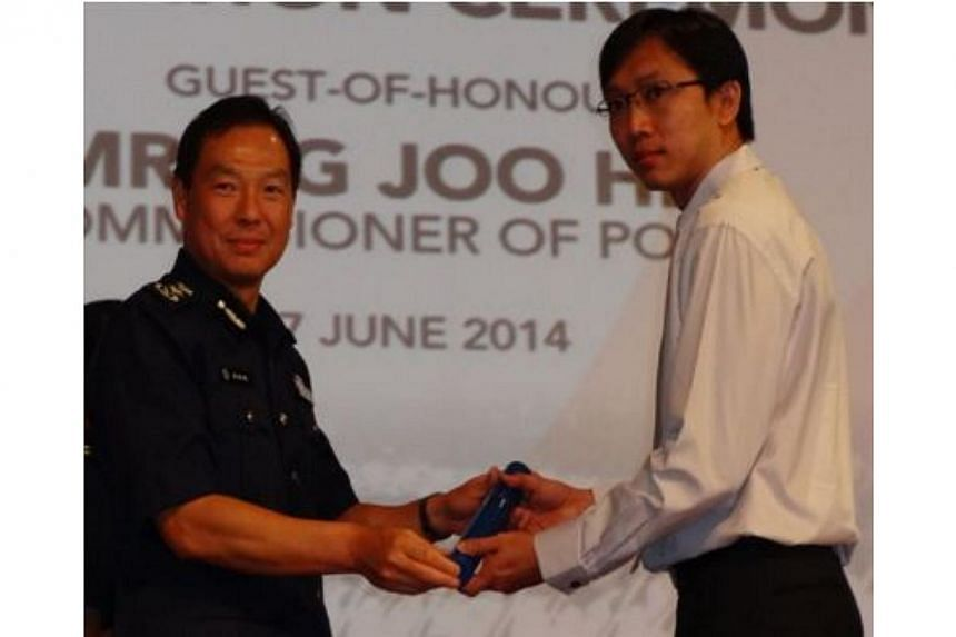 Commissioner of Police Mr Ng Joo Hee (left) presenting the Individual Commendation Certificate to Station Inspector (SI) Teng Chin Hock of the Commercial Crime Squad, Ang Mo Kio Police Division. SI Teng investigated a series of pawning of fake gold i