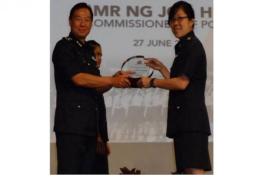 Deputy Superintendent of Police Tan Chin Yin (right) receiving the Most Improved Neighborhood Police Centre Award on behalf of Orchard Neighbourhood Police Centre. -- PHOTO: SINGAPORE POLICE FORCE