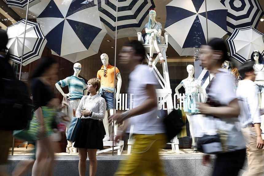 A woman stands in front of a luxury brand store as people walk past at a shopping district in Tokyo on June 26, 2014. -- PHOTO: REUTERS