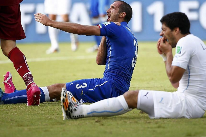 Uruguay's Luis Suarez (right) reacts after clashing with Italy's Giorgio Chiellini during their 2014 World Cup Group D soccer match at the Dunas arena in Natal in this June 24, 2014. -- PHOTO: REUTERS