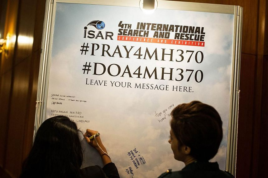 A visitor (left) writes on a placard carrying messages for the passengers of missing Malaysia Airlines flight MH370 during the 4th International Search and Rescue Conference and Exhibition (iSAR) in Kuala Lumpur on June 17, 2014. -- PHOTO: AFP