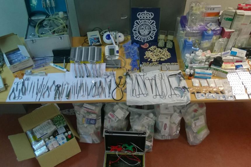 An undated handout picture released on June 27, 2014 by the Spanish National Police shows teeth, pills and numerous unsterilised forceps and dental tools seized at illegal Chinese clinics in Madrid. Spanish police busted a Chinese gang accused of car