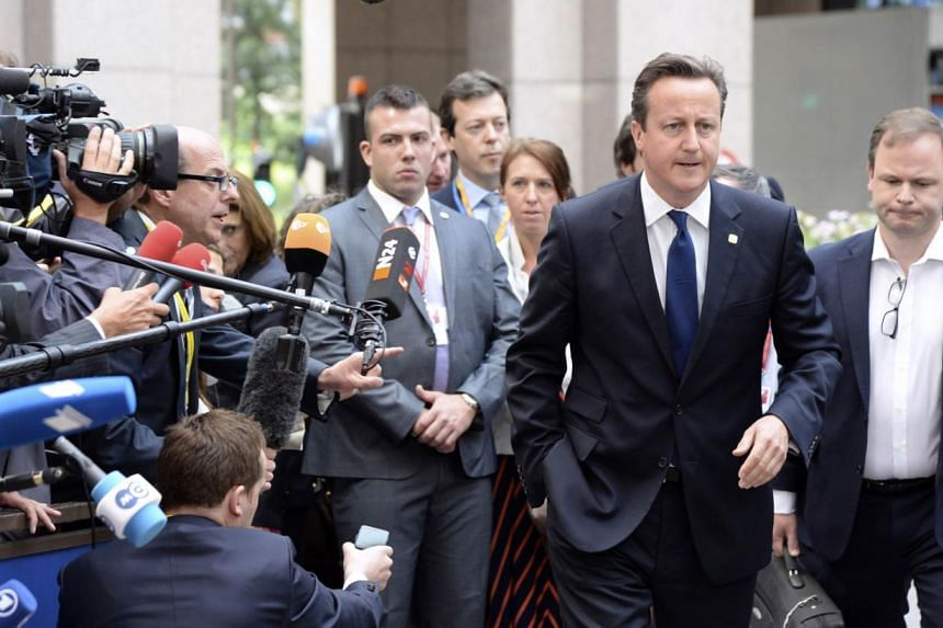 "British Prime Minister David Cameron (second from right) arriving for the second day of the EU summit on June 27, 2014 at the EU headquarters in Brussels. Mr Cameron on Friday said Jean-Claude Juncker was the ""wrong person"" to head the European Commi"