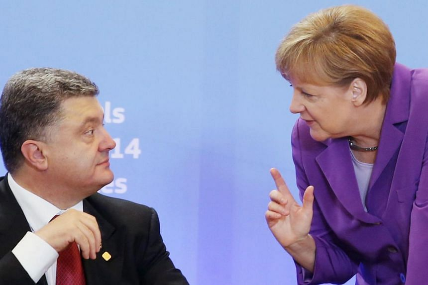 Ukraine's President Petro Poroshenko listening to Germany's Chancellor Angela Merkel during the cooperation agreement signing ceremony at the EU Council in Brussels on June 27, 2014. Ukraine signed a free-trade and political cooperation deal with the