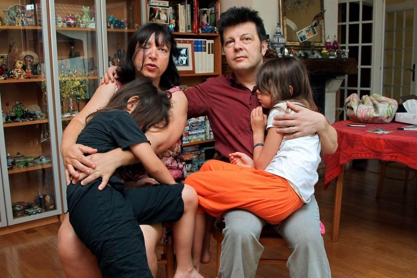 A photo taken on July 2, 2009, shows Sylvie and Dominique Mennesson, parents of twins born in 2000 from a surrogate mother from California, as they pose with their daughters at their home in Maison Alfort, France. They turned to theEuropean Cou