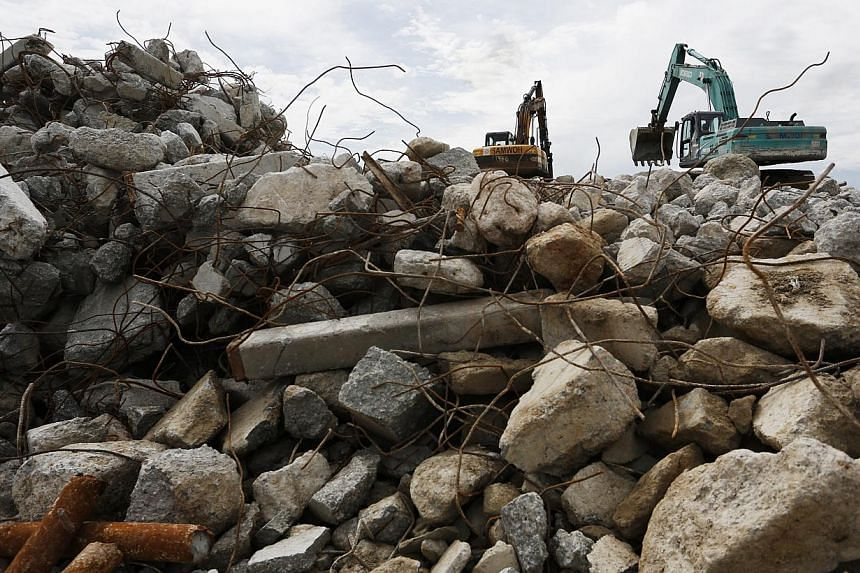 A conveyor belt delivers newly crushed rocks to be screened for sizes at Samwoh's recycling plant. The waste is processed into recycled concrete aggregate and used for road construction and production of non-structural concrete. Excavators sort out c